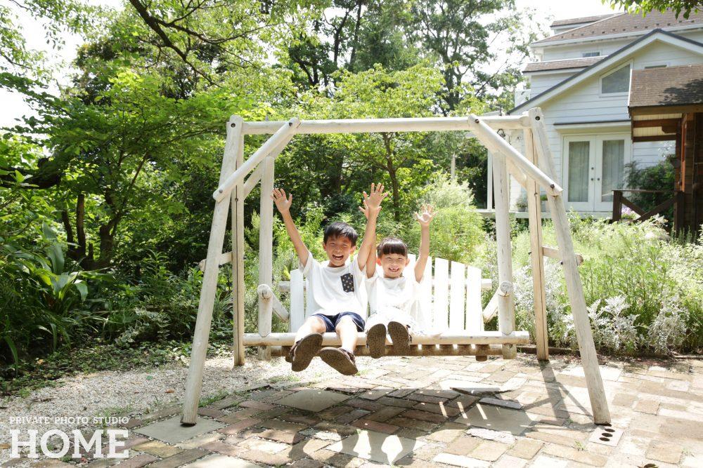 子供写真スタジオのStudioHOME鎌倉店で撮影した兄弟がブランコに乗っている写真。