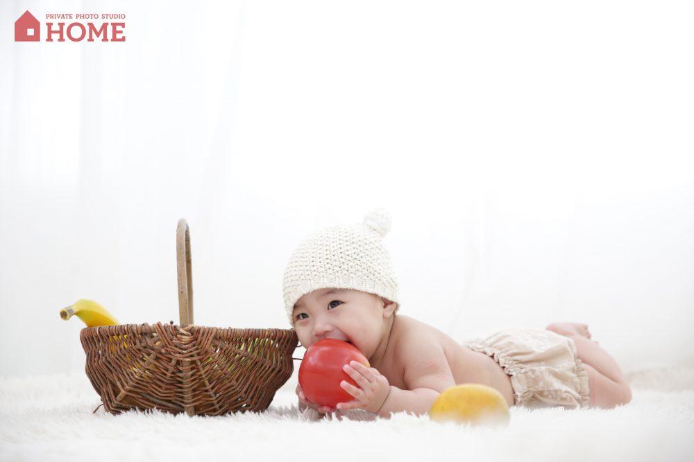 子供写真スタジオStudioHome鎌倉店で6ヶ月の女の子が玩具のりんごを咥えている写真。
